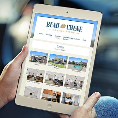 person holding a tablet showing Beau Chene Condominium's revamped Wordpress theme