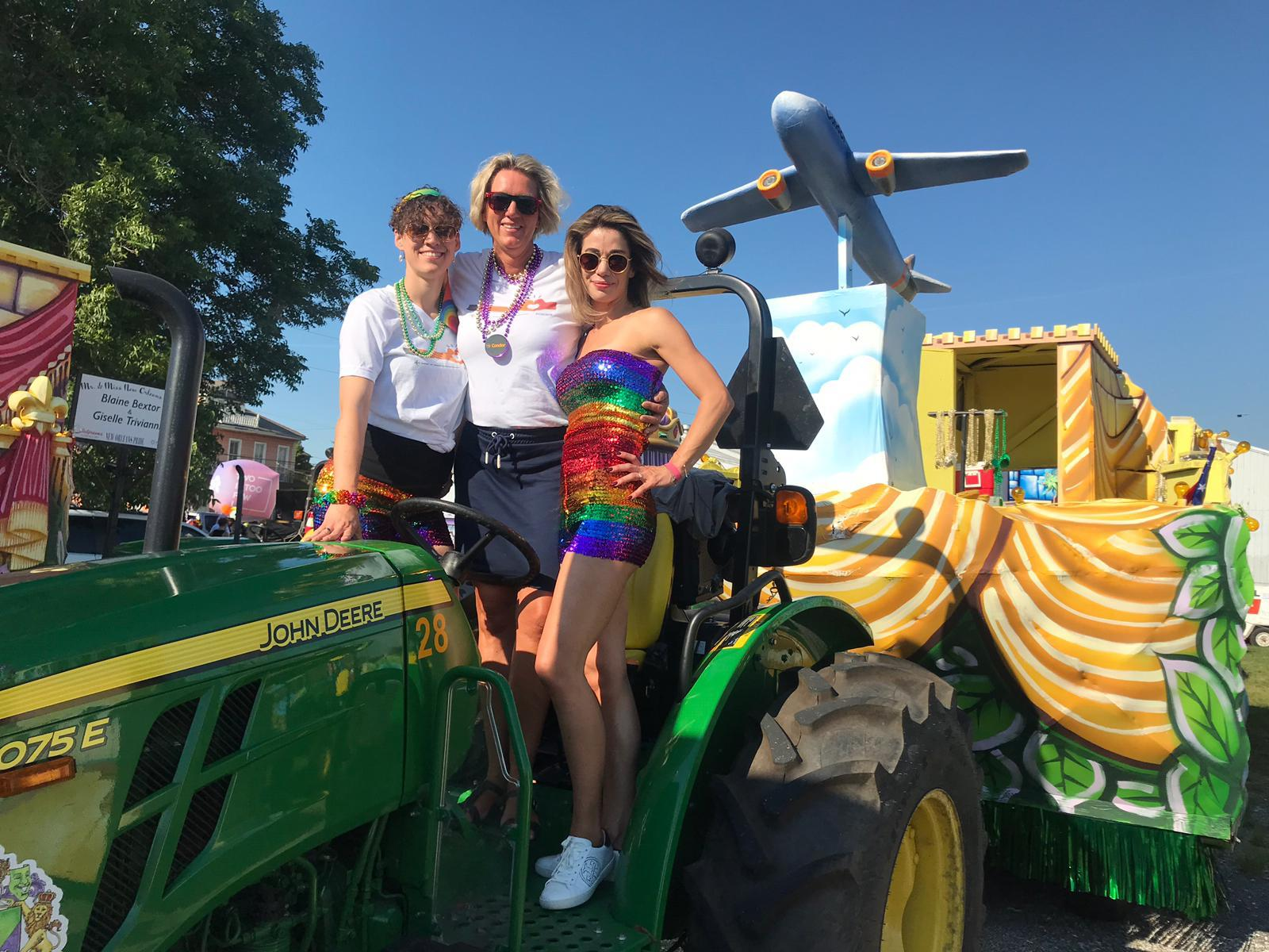 Condor pilots gathering at the helm of the tractor pulling a pride parade float